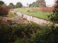 Photograph taken in September 1995, of all that remained then of the former swimming pool, built by the Royal Engineers stationed in Gilford Co Down during the war. This photo is taken looking North towards what would have been the shallow - 4feet 6inch end of the pool. When the pool was in use, a chute would have been situated to the right of this picture, and paving surrounded edges of the pool. The entrance door to the pool would have been behind the photographer. During the war the pool was extensively used for training and relaxation purposes, and for numerous competitions between various army regiments, airforce units etc. in Northern Ireland. Unfortunately today (2013) even these ruins are non-existent.